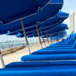 Umbrellas and empty beach couches at the beach — Foto Stock