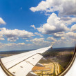 Lookout of aircraft window to landscape while landing — Stock Photo
