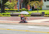 Attracive lady rides in her electric wheelchair with a parasol — Stock Photo