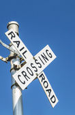Railroad warning crossing sign under blue sky — Stock Photo