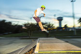 Boy has fun riding his push scooter at the skate park — Stock Photo