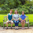 Happy family sits in the garden at a bench   — Stock Photo