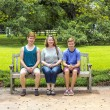 Happy family sits in the garden at a bench  and enjoys nature — Stock Photo