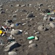 Stock Photo: Black vulcanic beach is littered by garbage of campers and touri
