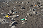 Black vulcanic beach is littered by garbage of campers and touri — Stock Photo