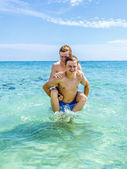 Teen have fun playing piggyback in the ocean — Stock Photo