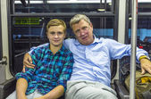 Father and son at the airport bus after arrival — Stock Photo