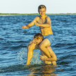 boys have fun playing piggyback in the ocean — Stockfoto