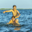 boys have fun playing piggyback in the ocean — Photo