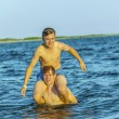 boys have fun playing piggyback in the ocean — ストック写真