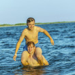 boys have fun playing piggyback in the ocean — Foto Stock