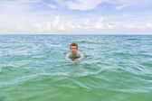 Teenage boy enjoys swimming in the ocean — Foto Stock