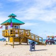 People enjoy the beach at sunny isles protected by lifeguards in — Stock Photo