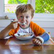 Young boy with arm in cast has breakfast at the table — Stock Photo