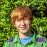 Portrait of attractive happy smiling boy in the garden — Stock Photo #32544499