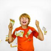Euros flying around a boys head — Stock Photo