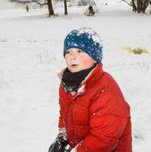 Chico parece feliz de jugar en la nieve — Foto de Stock