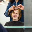 Smiling young boy with red hair at the hairdresser — Stock Photo #32924023