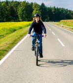 Boy on a biycle ride on a small street in the countriside of Bav — Stock Photo