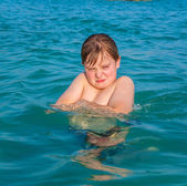 Boy enjoys the clear warm water but looks angry — Stock Photo