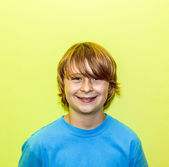 Happy smiling young boy with yellow wall — Stock Photo