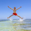 Happy boy jumps in the air over the ocean — Stock Photo #33832121