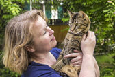 Woman holds her tiger cat in the arm — Stock Photo