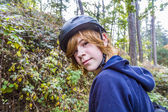 Young teenage boy in forest with bike helmet — Stock Photo