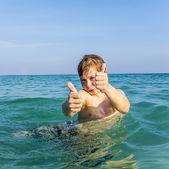 мальчик любит океан и показывает большие пальцы вверх — Стоковое фото
