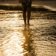 Feed of walking man at the beach in backlight — Stock Photo