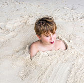 Young boy covered by fine sand at the beach — Stock Photo