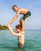Brothers playing piggyback in the ocean — Stock Photo
