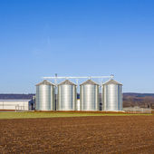 Landscape with silo and snow white acre with blue sky — Stock Photo