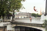 Children jump from a bridge in the river — Stockfoto