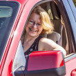 Smiling woman drives a red car — Foto de Stock
