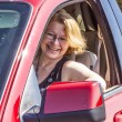 Smiling woman drives a red car — Stock fotografie