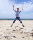 Boy enjoys the beautiful beach and jumps — Stock Photo