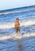 Mladý chlapec běží ve vodě na pláži — Stock fotografie