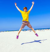 Boy enjoys jumping in the air at the beach — Stock Photo