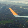 Wing of aircraft with aerial of Hamburg — Stock Photo