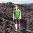Stock Photo: Boy walking in volcanic area
