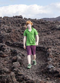 Boy walking in volcanic area — Stock Photo