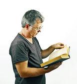 Hombre con gafas de lectura en un libro — Foto de Stock