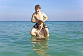 Brothers enjoy the clear warm water and playpickaback — Foto de Stock