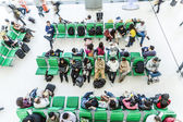 Passengers wait on benches for the departure of their flight — Stock Photo