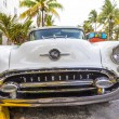 Постер, плакат: Classic Oldsmobile with chrome radiator grill parked in front o