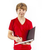 Boy with red shirts writes in his book — Stock Photo