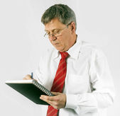 Serious business man writing in a book — Stock Photo