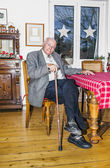 Old Grandfather sitting with his walking stick at the table — Stock Photo