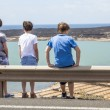 Stock Photo: Three boys leaning at guide rail